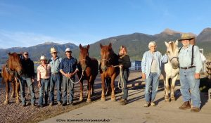 Several students and horses posing for a group shopt at the conclusion of a horsemanship workshop